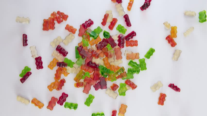 Colorful gummy bears falling in slow motion full HD footage top view