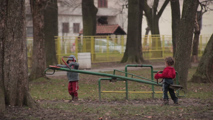 Children brother and sister playing game in the park. Two little gypsy kids sitting on a seesaw in the playground. Childhood, gypsy, ethnic, marginalized group, poor, poverty, misery, life in ghetto.