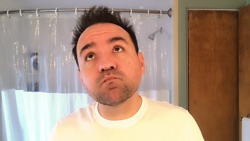 A tired and groggy man uses mouthwash in the morning while looking at himself in the bathroom mirror.