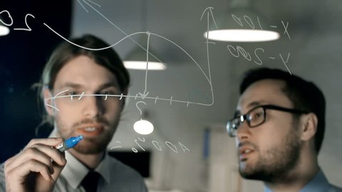 Close up of two men in formalwear deriving formula and writing on glass board