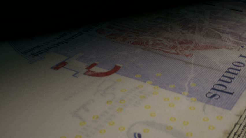 An extreme closeup of  british pound banknotes flipping through in a counting machine