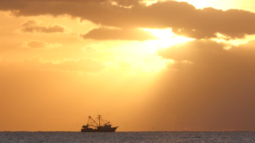 A Commercial Fishing Boat At Sea Catching Fish As The First Sun Appears At Sunrise From Behind Clouds Creating A Heavenly Light Ray.