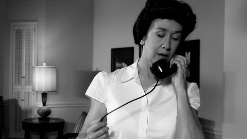 A 1940s era scene of a woman engaged in conversation on a vintage time period telephone. Film Noir, black and white.