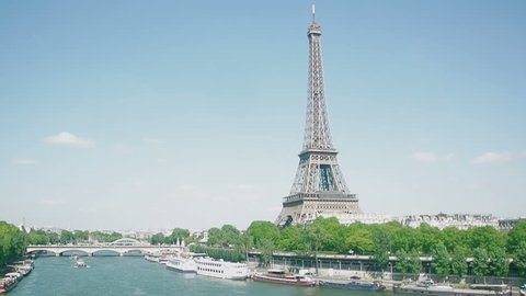 Famous Eiffel Tower, beautiful Seine River, streets, buildings and homes with in heart of Paris seen by a cinematic flying drone in the sky over the tourism symbol of French capital