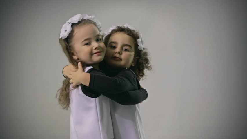 Good looking and loving twins. Little sisters. Smiling, hugging, playing, smiling, dancing, running.  Adorable. Happy lifestyle kids.