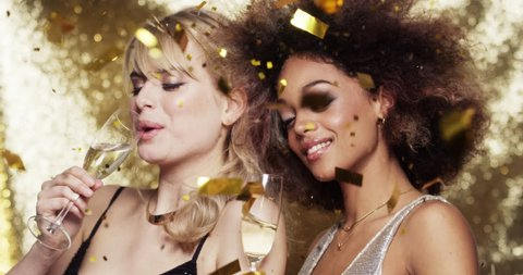 Girlfriends celebrating new years party drinking champagne dancing gold glitter background - Red Epic Dragon