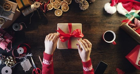 Top view woman unwrapping christmas presents at wooden desk hands from above - Red Epic Dragon