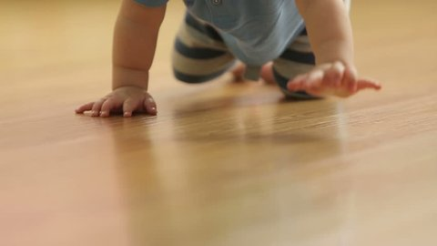 baby crawling on the floor, back view, slowmotion