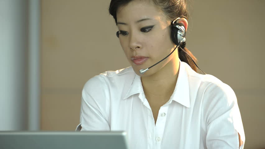 Chinese businesswoman at callcenter, then looking at camera and smiling; Nikon D3S, HD: Photo JPEG.