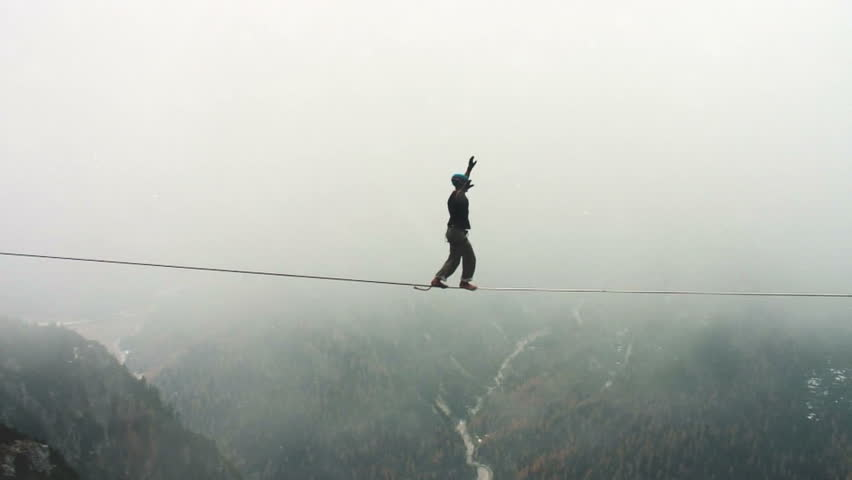 aerial shot of tightrope walker in the air in the mountain with snow and wind