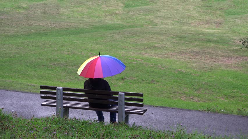 Man with rainbow umbrella sitting on isolated bench in the park, waiting