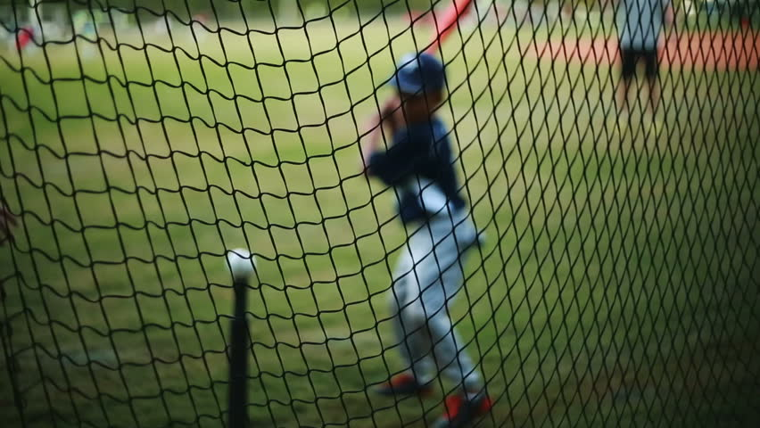 Shot from behind net of a Kid Practicing his Batting on a Baseball Field