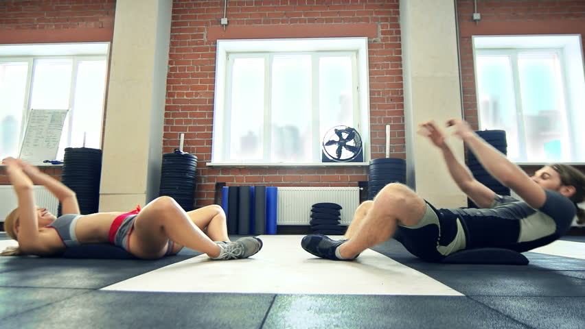 Side view of coach encouraging sportswoman to finish the set of situps in a gym   Shutterstock HD Video #9041584