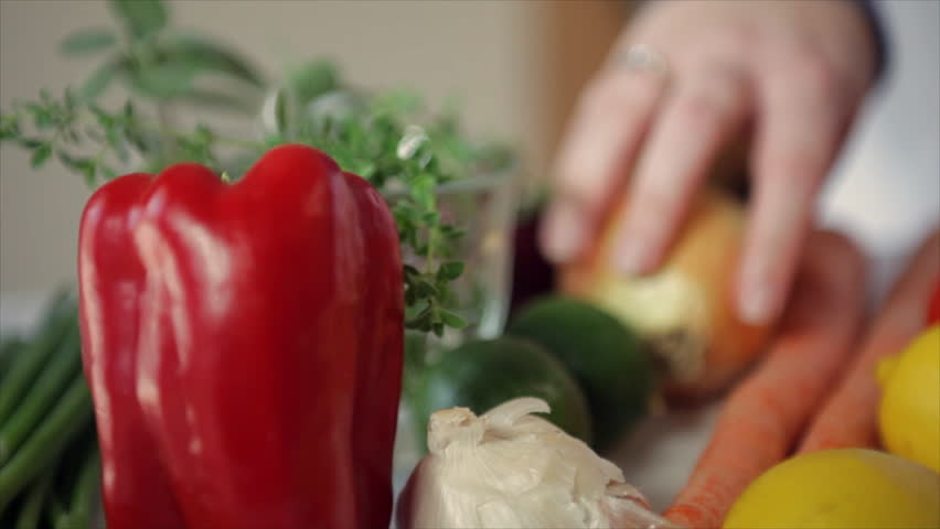 The camera pans across a variety of vegetables to focus on a woman peeling a flavorful yellow onion. Pan, Tilt, Rack focus.