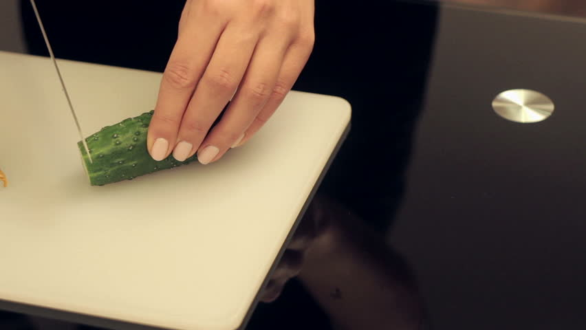 woman cuts cucumbers on cutting board for salad #9076424