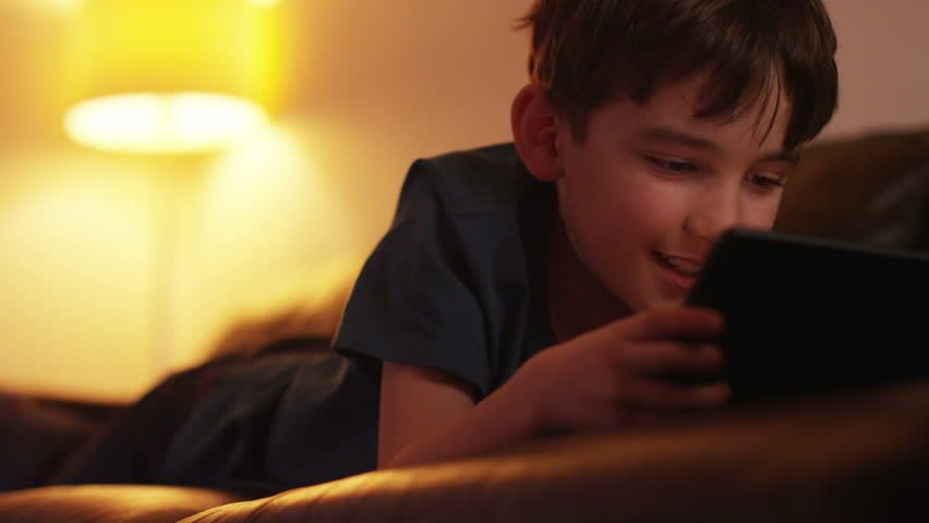 Young boy using tablet while lying down on couch at home. 4k Dolly shot. | Shutterstock HD Video #9077714