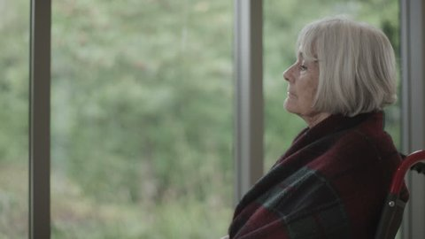 4K Portrait of lonely senior lady sitting by the window & looking over to her medication