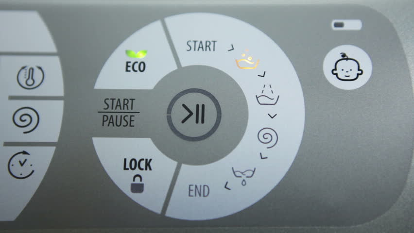 """Women's hand presses the """"Start"""" button on the washing machine."""