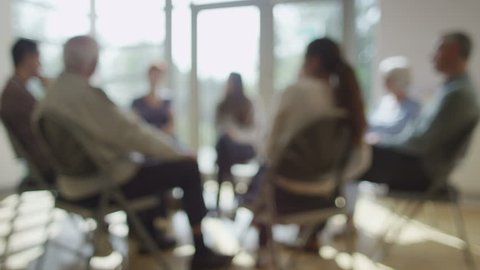 4K People in group therapy session talk about their problems in sunlit room.