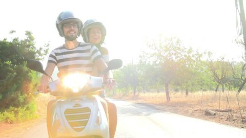 Slow motion sequence of young couple riding motor scooter along country road.Shot on Sony FS700 at frame rate of 100fps