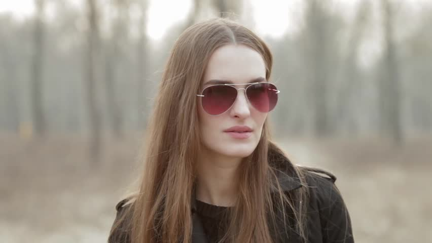a970d465a3 Young beautiful fashionable woman in sunglasses answer a mobile phone call  in spring forest park