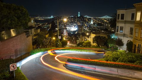 Time lapse looking down Lombard street in San Francisco. The Bay Bridge and Coit Tower can be seen in the background. Camera view centered on the street.