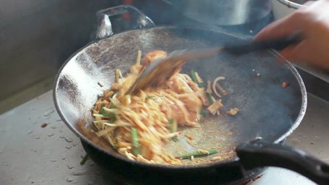 Chef cooking Pad Thai stir-fried rice noodles with shrimp in pan