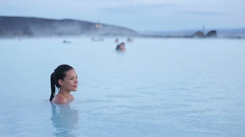 Hot spring pool - woman relaxing in geothermal spa on Iceland. Girl enjoying bathing in a blue water lagoon Icelandic tourist attraction. Portrait of mixed race Asian Caucasian female model at sunset.