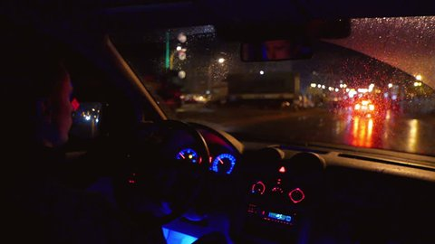 The man drive the car (chase), inside view, control panel, wheel, wide angle. Evening-night time, real time capture
