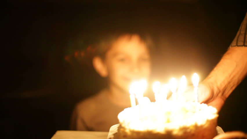 boy blows out candles on birthday cake.