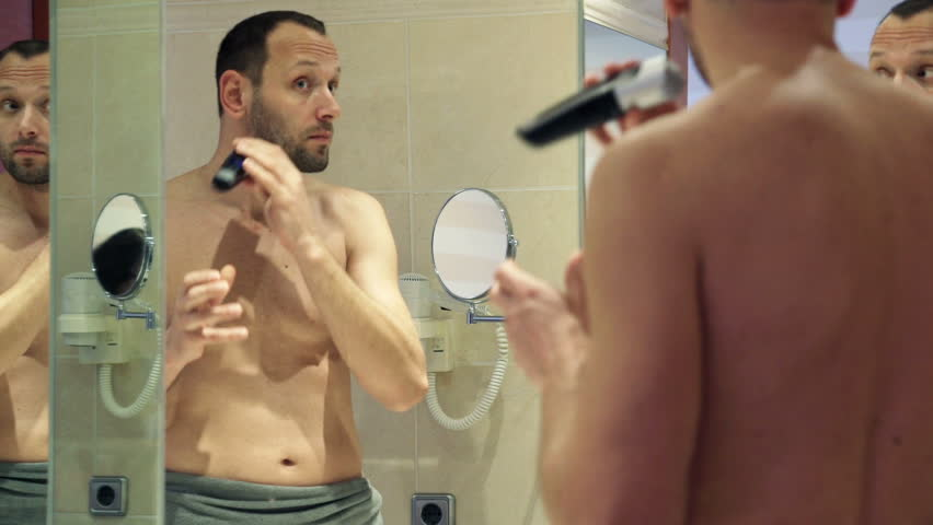 Young man shaving his beard with electric shaver in the bathroom