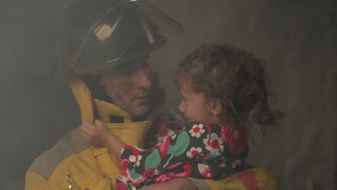 Fireman holding a young girl