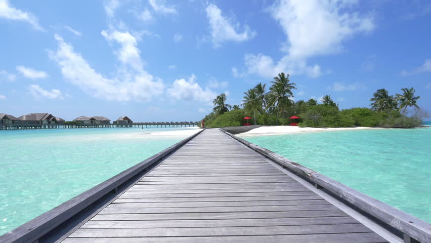 SLOW MOTION: Water villas in front of exotic white sand beach