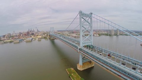 Cityscape with Benjamin Franklin Bridge across Delaware river at autumn cloudy day. Aerial view