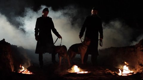 Military men go with trained dogs at night.