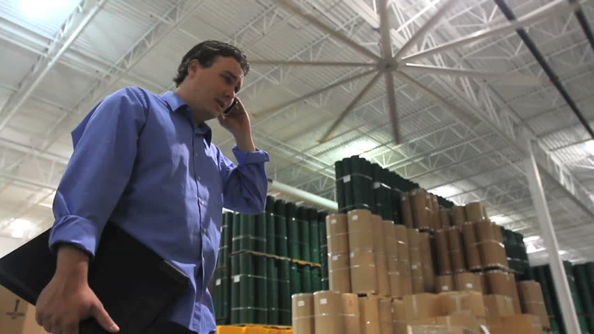 A supervisor talks on his phone in the middle of a large industrial warehouse.