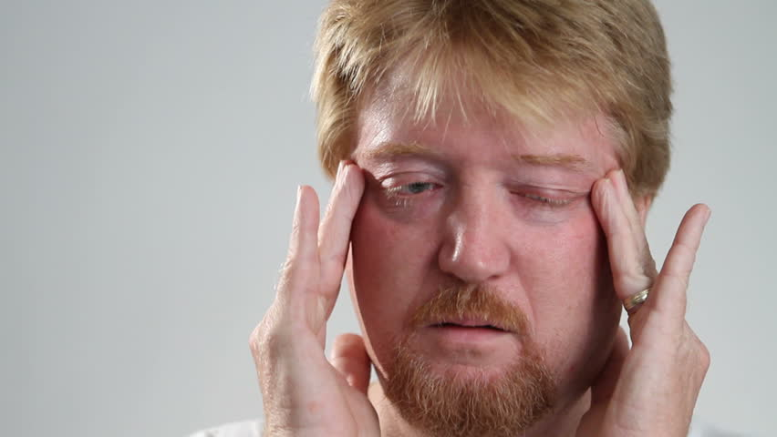 Man rubs his temples to relieve his headache pain.
