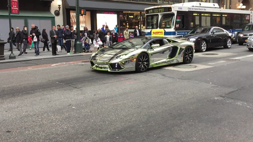 New York City - April 2015: Lamborghini with mirrored finish drives down 34th street to the 2015 New York International Auto Show at the Jacob K. Javits Convention Center in Manhattan.
