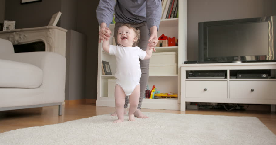 One year old baby having fun learning to walk