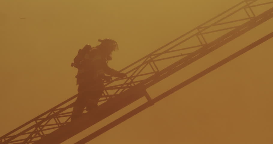 Fireman with self-contained breathing apparatus climbing aerial ladder through thick heavy smoke above fire | Shutterstock HD Video #9488114