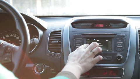 Human driving car and pushing buttons on radio, dashboard and wheel with speedometer