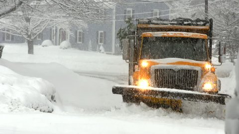 Orange city snow plow coming towards camera on residential street  in a heavy snow storm