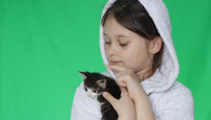 Cute little girl in white bathrobe is holding a kitten on a green screen   Shutterstock HD Video #9513464