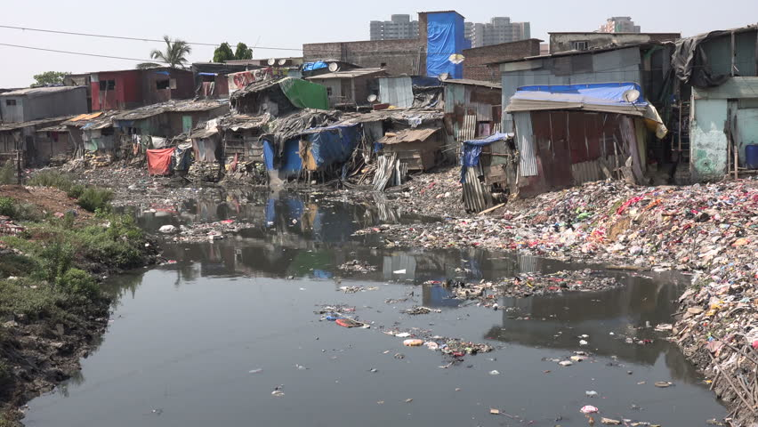 MUMBAI, INDIA - 9 NOVEMBER 2014: Polluted water and a small garbage dump in front of slum housing in Mumbai.