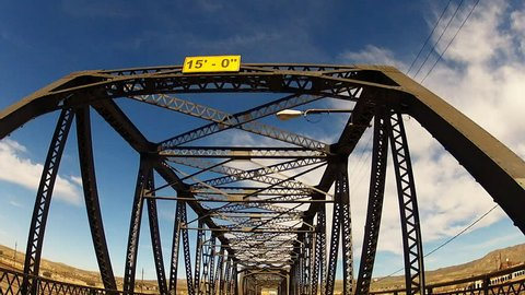 BARSTOW, CA/USA: March 6, 2015- A low angle vehicle mounted camera crosses a bridge and looks up at the old style iron trusses and sky. An iconic road trip visual.