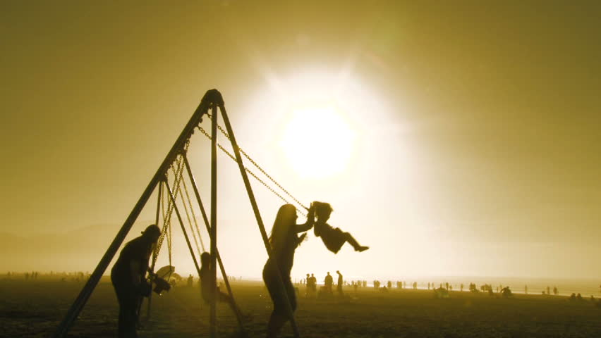 SEASIDE, OREGON - CIRCA 2015: Silhouettes of mother and daughter enjoying beautiful sunny day playing on swing set in Oregon.   Shutterstock HD Video #9522884