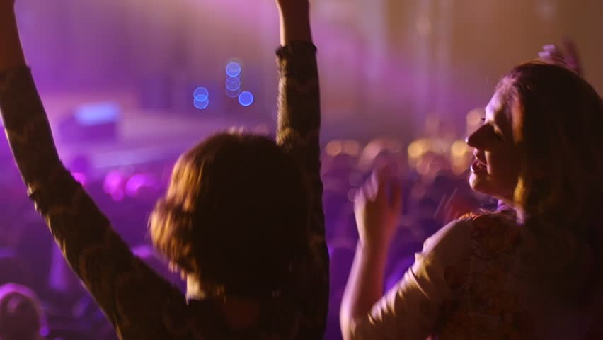 Dancing girl fan silhouettes on concert flashing light cheerful hands in air #9528029