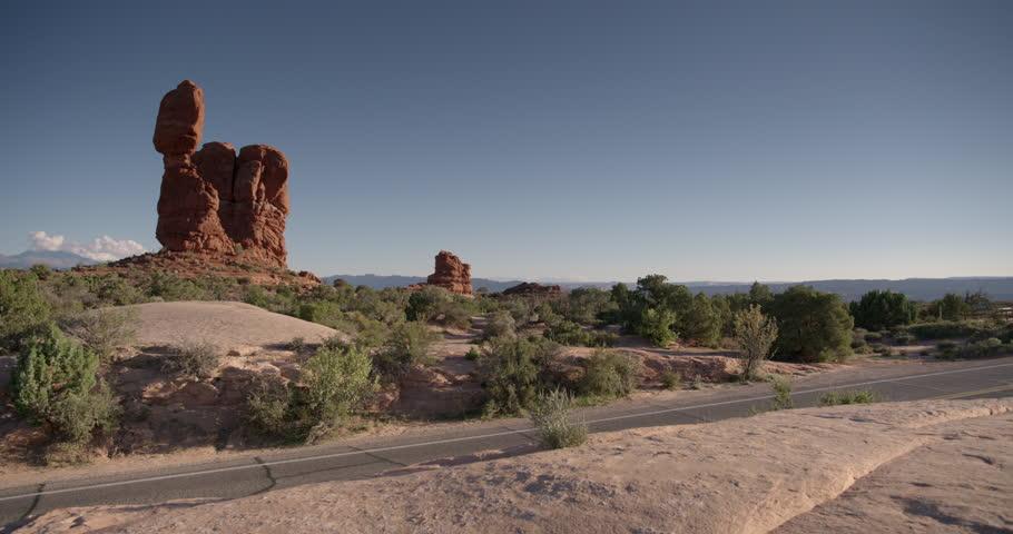 Arches National Park Moab Utah Cars Driving Past Balanced Rock At Sunset