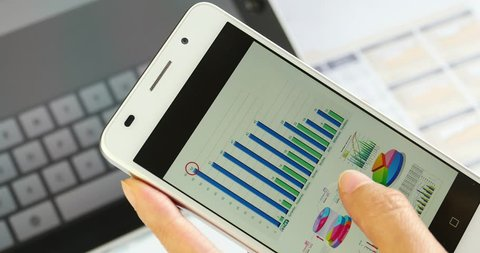 4k Business people browsing finance pie charts & stock trend on smartPhone,ipad virtual-keyboard & data paper background. gh2_10979_4k
