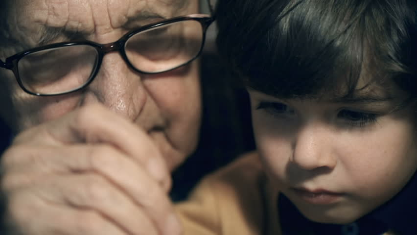 Tilt down the faces of a boy and his grandfather to watch screwdriver and wristwatch details